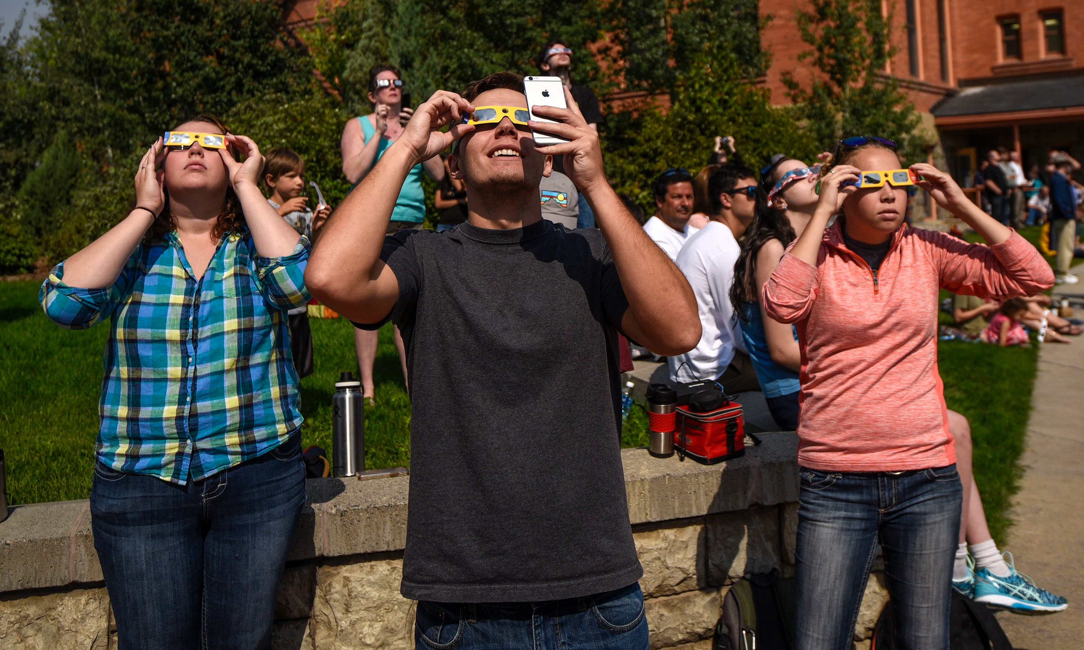 BOZEMAN, MT - AUGUST 21:  Students and onlookers look toward the sun through eclipse glasses on the campus of Montana State University on August 21, 2017 in Bozeman, Montana.  (Photo by Leigh Vogel/WireImage)