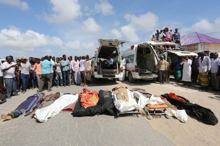 Relatives stand near the bodies of civilans killed in an attack by Somali forces and supported by U.S. troops on Aug. 25.
