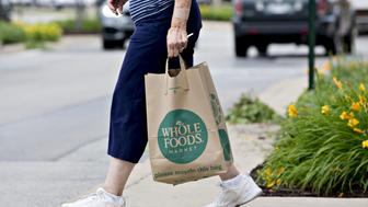 A customer carrying a shopping bag exits a Whole Foods Market Inc. location in Naperville, Illinois, U.S., on Friday, June 16, 2017. Amazon.com Inc. will acquire Whole Foods Market Inc. for $13.7 billion, a bombshell of a deal that catapults the e-commerce giant into hundreds of physical stores and fulfills a long-held goal of selling more groceries. Photographer: Daniel Acker/Bloomberg via Getty Images