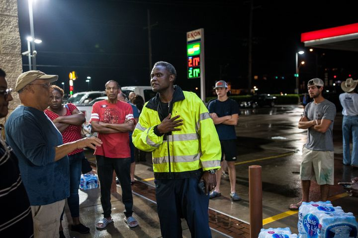 Beaumont ISD Police Chief Joe Malbroughattempts to stop people from taking water outside a local convenience store.