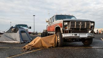 A rescurer sleeps in a lawn chair, covering themselves with a blanket in the parking lot of the Central Mall in Port Arthur, TX on Thursday morning.
