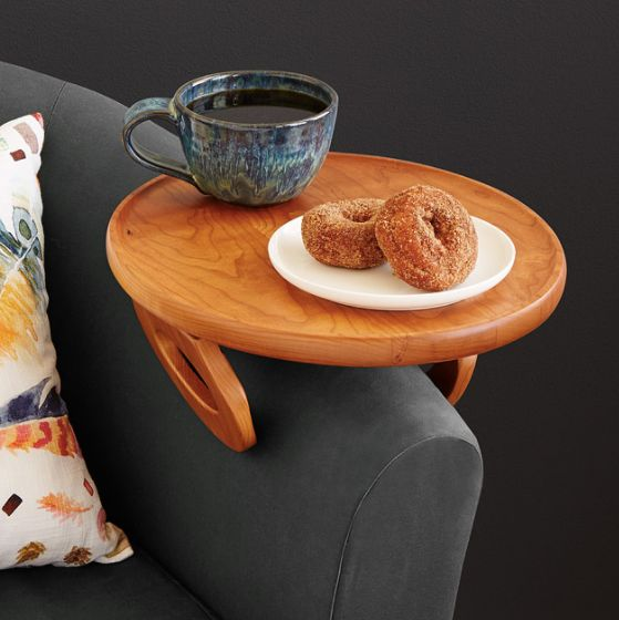 """<a href=""""https://www.uncommongoods.com/product/couch-arm-table"""" target=""""_blank"""">Shop it here</a>."""