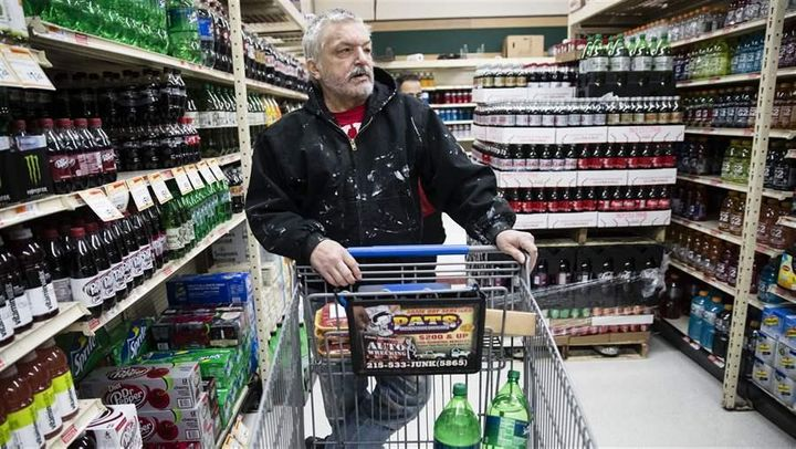 A customer shops for soda in Philadelphia, where beverages are subject to a new tax. The beverage taxes were aimed at sugary