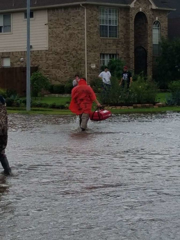 A man delivers pizza to a home surrounded by water.