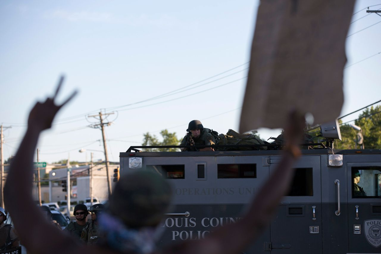 A police officer aims his weapon at a demonstrator in Ferguson, Aug. 13, 2014.