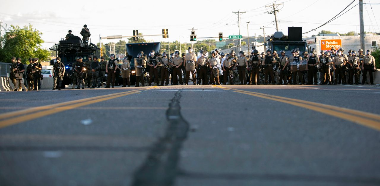 Police officers keep watch while demonstrators (not pictured) protest the death of black teenager Michael Brown in Ferguson, Missouri, Aug. 12, 2014.