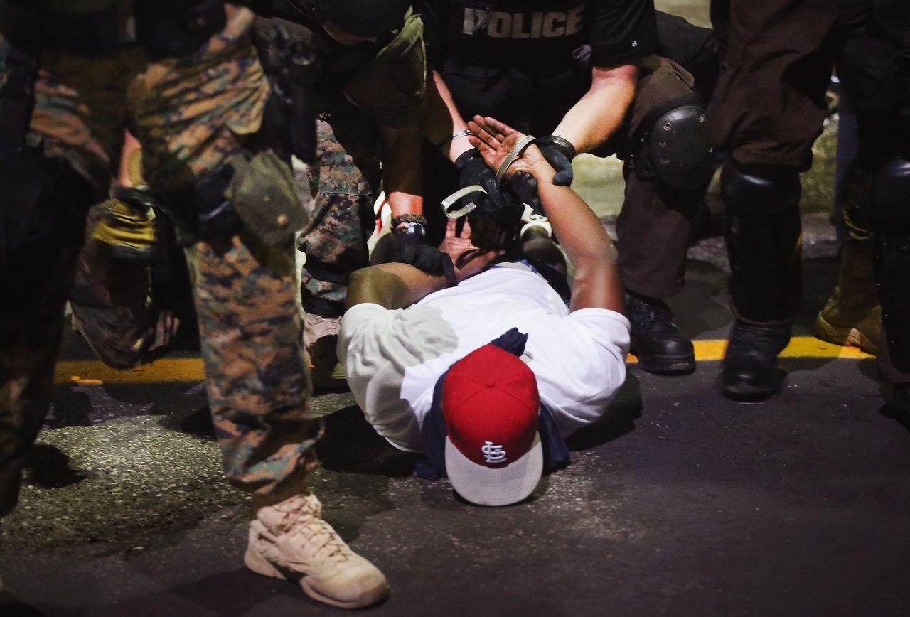 Police arrest a demonstrator in Ferguson on Aug. 19, 2014.