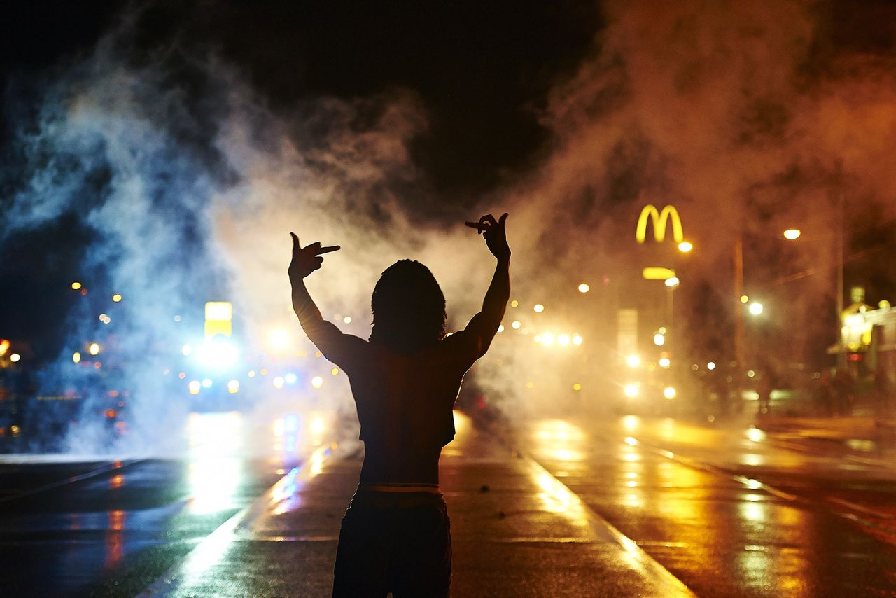 A protester gestures angrily at cops as tear gas fills the streets of Ferguson after curfew early Sunday, Aug. 17, 2014.