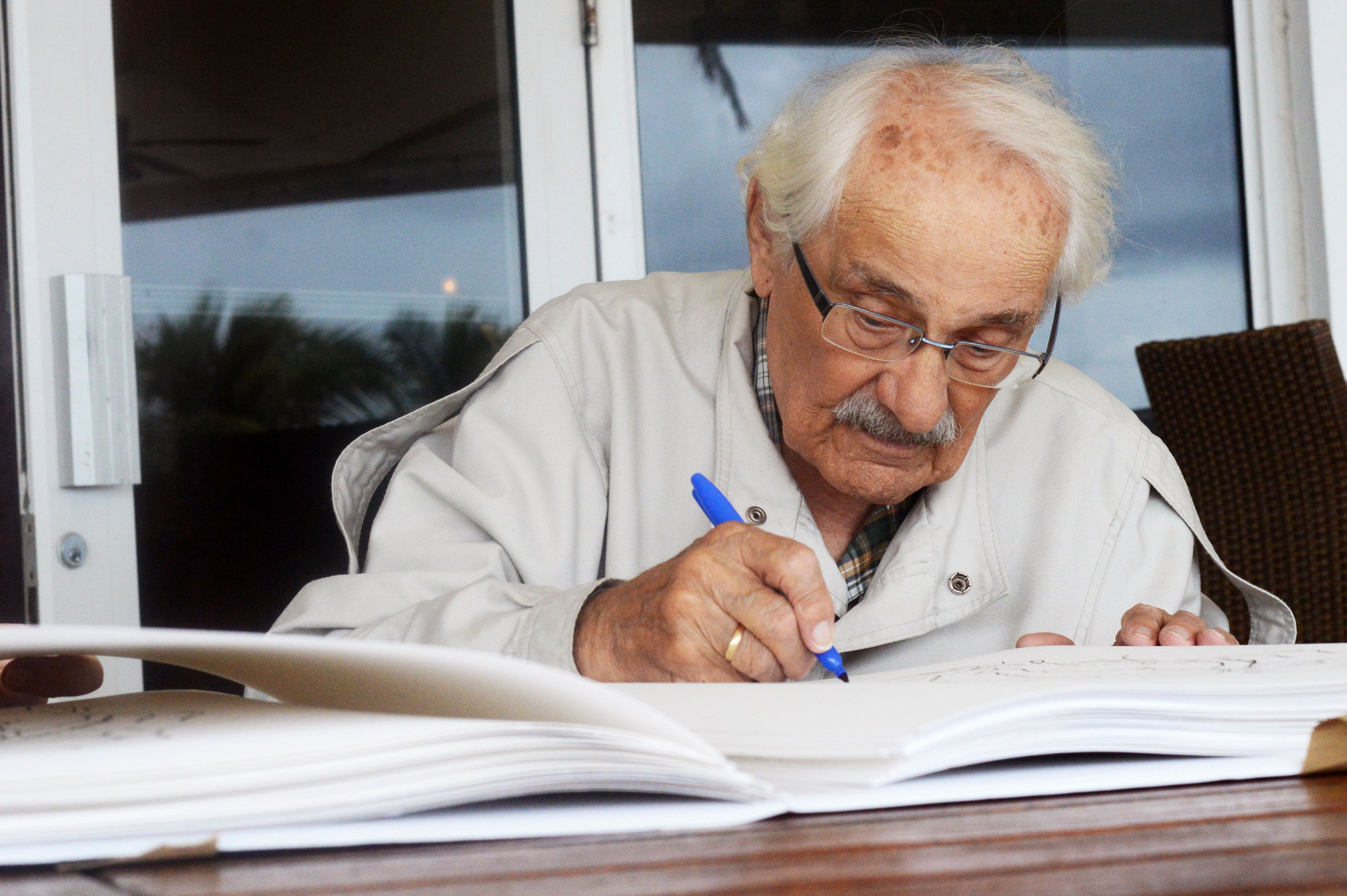 Samuel Willenberg, 92, the last known survivor of the Nazi extermination camp Treblinka in Poland and the subject of a film on the camp produced by Alan Tomlinson, signs sketches of one of his sculptures of scenes at Treblinka, in Miami Beach, Florida October 23, 2014. Willengberg began creating the sketches, which he recalls from his memory there, at the age of 70 after he retired. REUTERS/Zachary Fagenson    (UNITED STATES - Tags: ENTERTAINMENT CONFLICT)