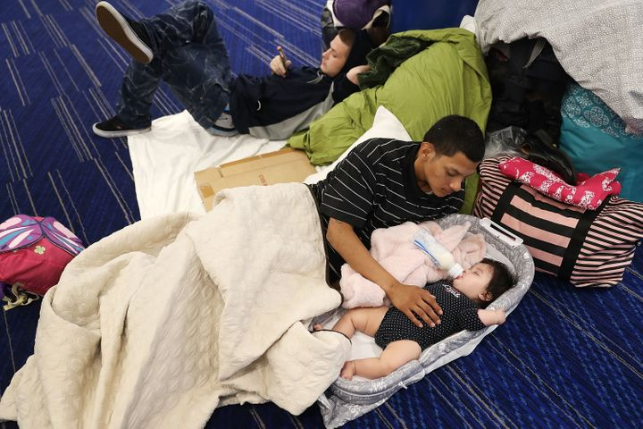 Mark Ocosta and his baby, Aubrey Ocosta, take shelter at the George R. Brown Convention Center after floodwaters inundated&nb