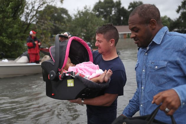 A rescue worker carries a baby to dry land in Port Arthur, Texas, on Aug. 30,