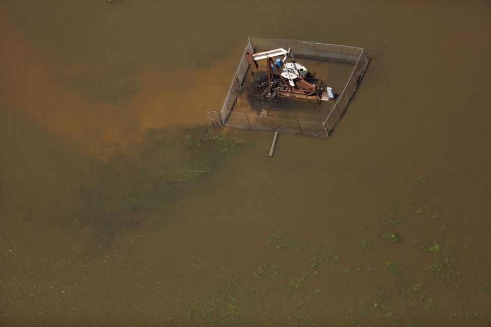 A pump jack oil well is seen immersed in floodwaters.
