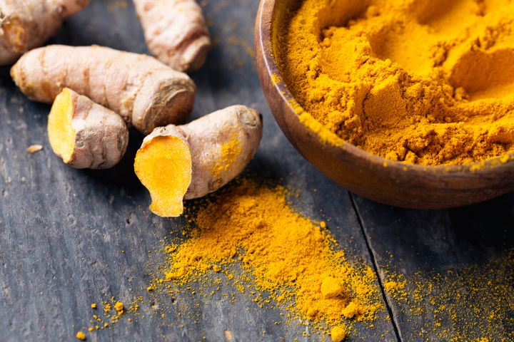 Fresh turmeric roots and turmeric powder in a wooden bowl.