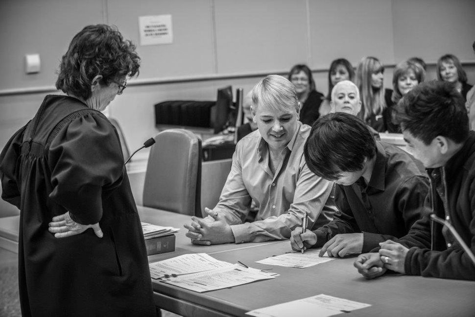 Judge Marta Diaz watches over as Tom Bauer (left) and his husband, Nilo Ventura (far right) sign the adoption papers with Jon Cardoza.