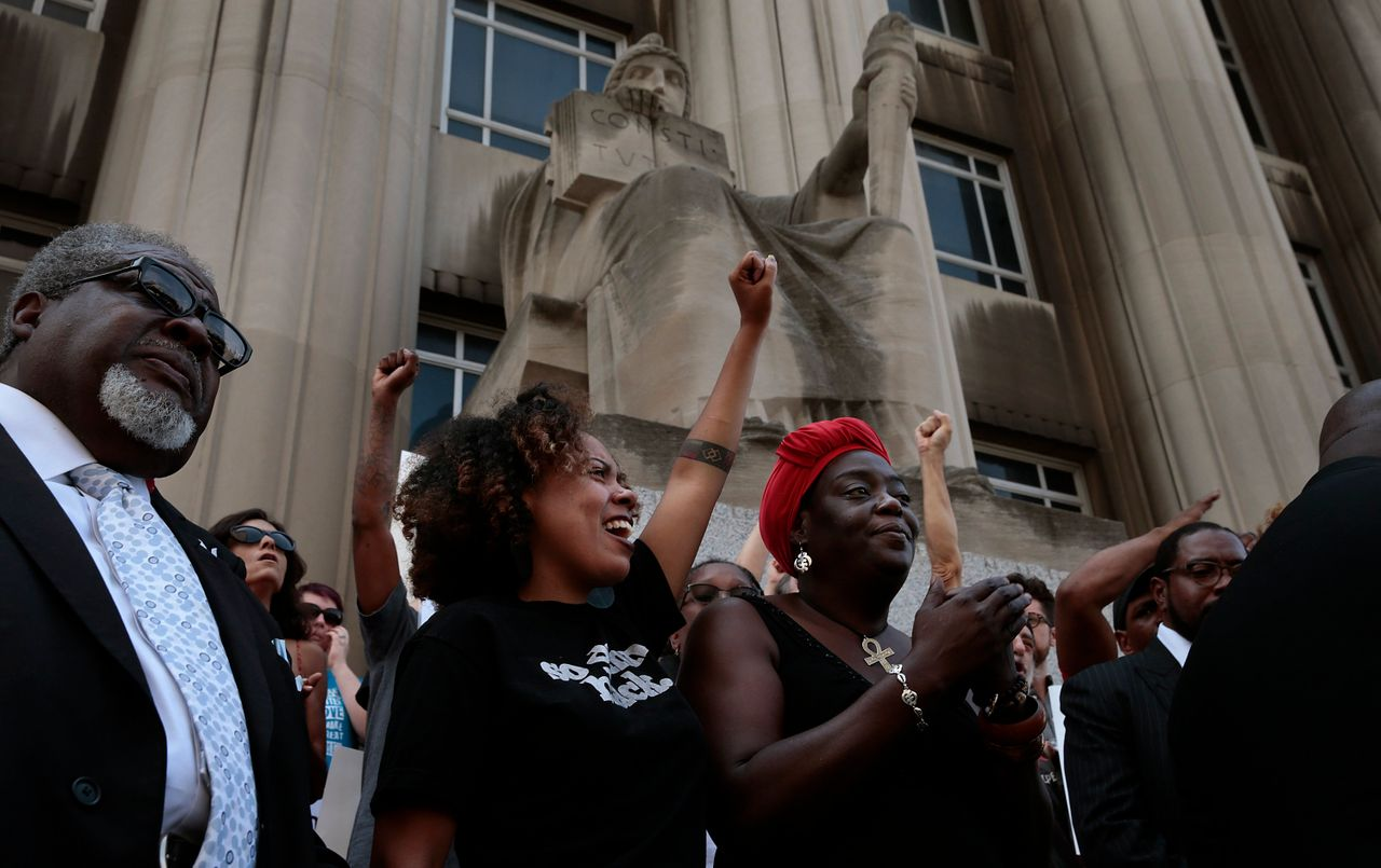 LaShell Eikerenkoetter, center, and Julia Davis cheer the words of area clergy who called for a guilty verdict in the shooting death of Anthony Lamar Smith by former St. Louis police Officer Jason Stockley.