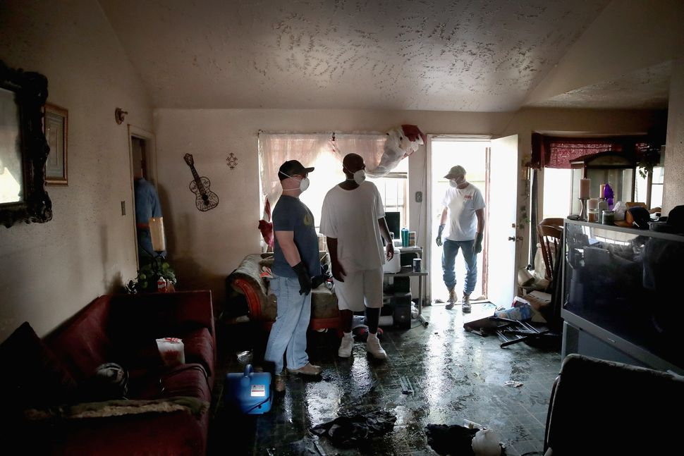 People on cleanup duty look around a damaged property.