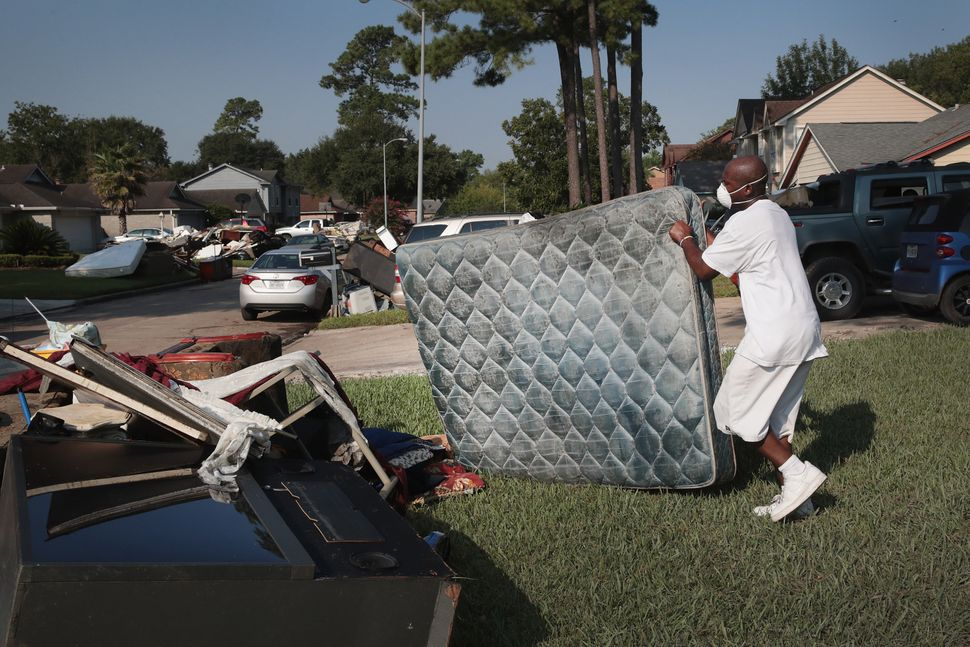 Cornell Beasley joins other residents as they dry and toss out their possessions.