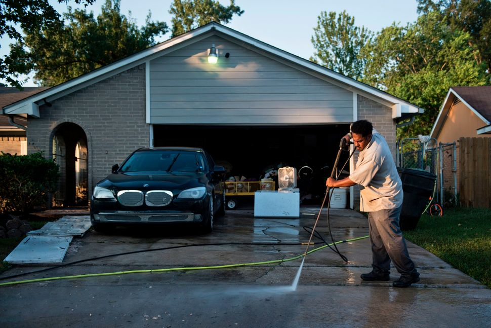 A man power-washes the driveway of his once flooded home.