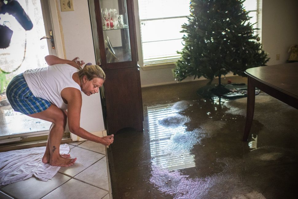 Missy Givens inspects the water level in her home.