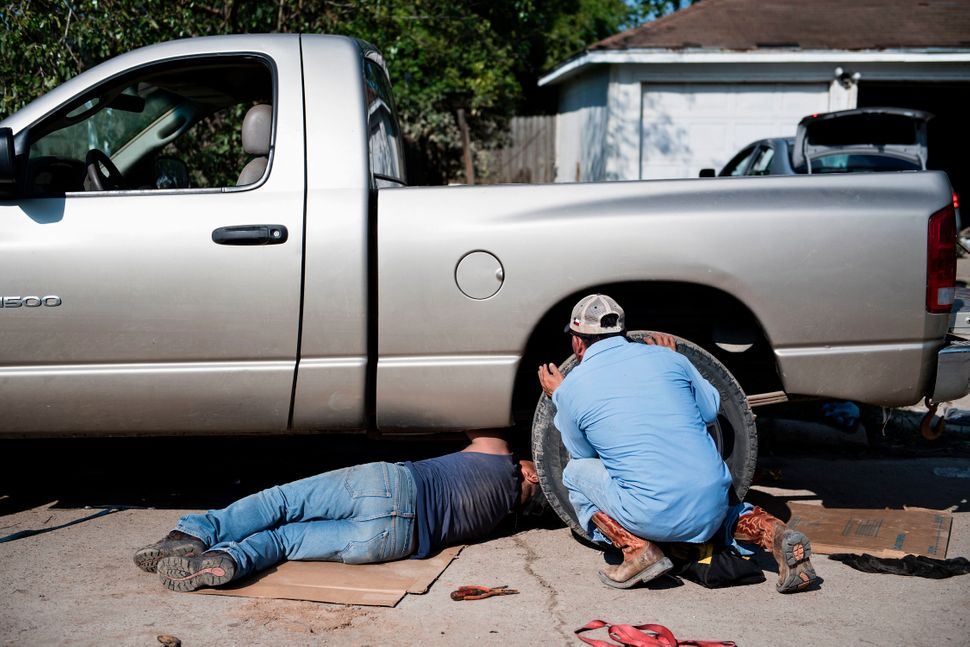 People try to repair a truck that was submerged in floodwater.