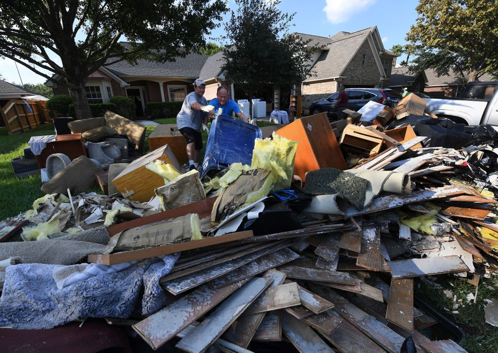 Family members remove debris and damaged items from their father's home.