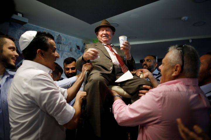 Shalom Shtamberg, a 93-year old Holocaust survivor, is lifted on a chair during celebrations marking his bar mitzvah ceremony