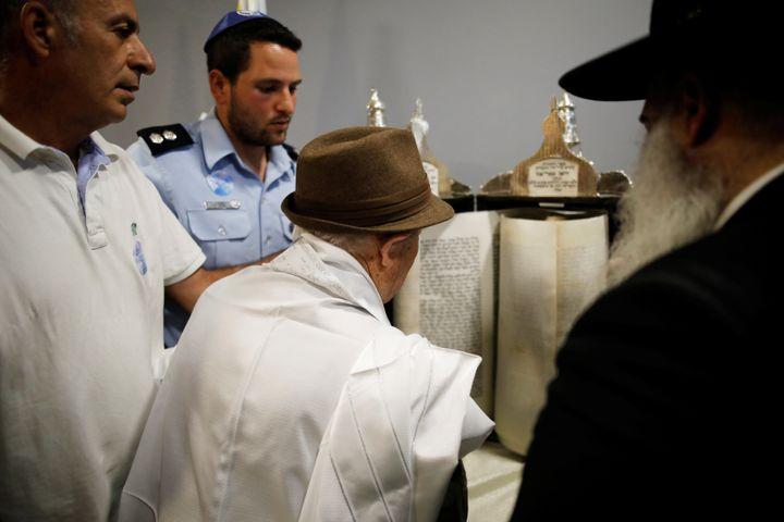 Shtamberg reads from a Torah scroll.