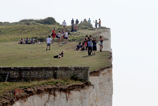 People on the cliffs at Birling Gap in Eastboune, Sussex, part of a stretch of coastline that was evacuated...