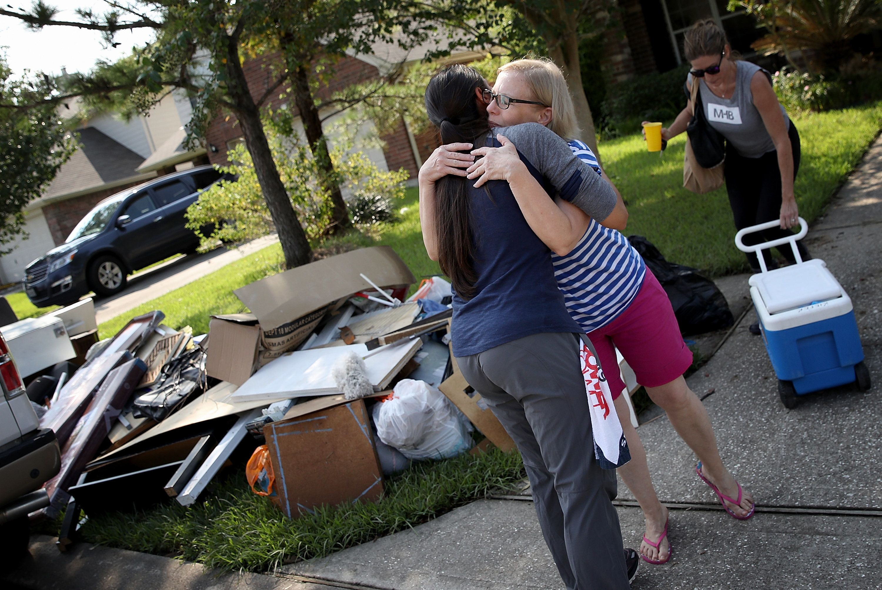 DICKINSON, TX - SEPTEMBER 01:  A Dickinson resident hugs a friend who came to help her remove possessions damaged by flooding brought on by Hurricane Harvey September 1, 2017 in Dickinson, Texas. Dickinson was hit by Hurricane Harvey extremely hard with major flooding in many areas of the city and residents there are beginning the long process of recovering from the storm.  (Photo by Win McNamee/Getty Images)