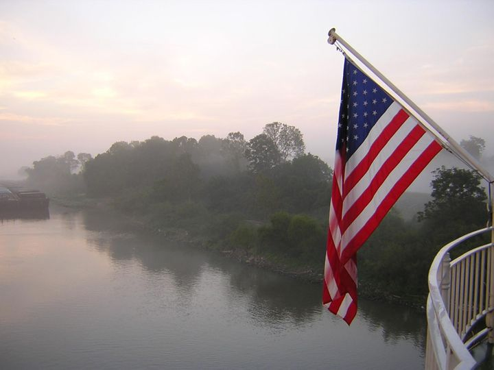 An American Flag in the early morning light near a levee on the Mississippi River.