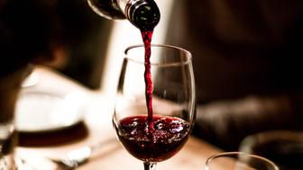 Red wine being poured into a stem glass at the table.