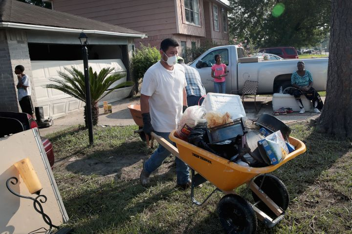 Volunteers from Performance Contractors help a co-worker clean up the damage to his Houston home after Hurricane Harvey.