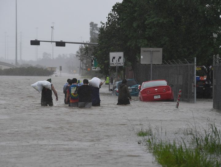 People walk through water to escape from their homes on Highway 90 after Hurricane Harvey caused heavy flooding in Houston, T