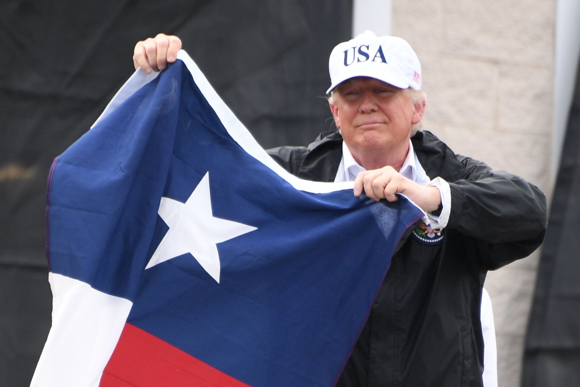 US President Donald Trump holds the state flag of Texas outside of the Annaville Fire House after attending a briefing on Hurricane Harvey in Corpus Christi, Texas on August 29, 2017. President Donald Trump flew into storm-ravaged Texas Tuesday in a show of solidarity and leadership in the face of the deadly devastation wrought by Harvey -- as the battered US Gulf Coast braces for even more torrential rain.   / AFP PHOTO / JIM WATSON        (Photo credit should read JIM WATSON/AFP/Getty Images)