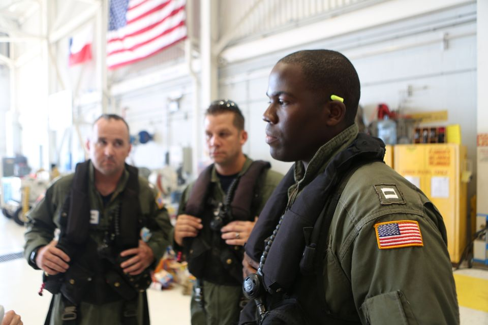 Coast Guard pilot Jason Brownlee, at right, is seen with commander John Egan, left, and flight mechanic...