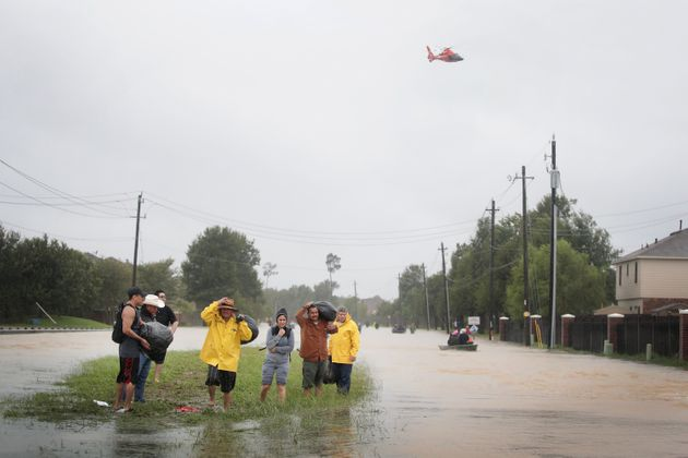 Residents make their way out of a flooded neighborhood in Houston on Monday. President Donald Trump...