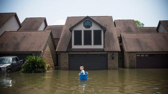 TOPSHOT - Jenna Fountain carries a bucket down Regency Drive to try to recover items from their flooded home in Port Arthur, Texas, September 1, 2017. Storm-weary residents of Houston and other Texas cities began returning home to assess flood damage from Hurricane Harvey but officials warned the danger was far from over in parts of the battered state. / AFP PHOTO / [Assignment # goes here] / Emily Kask        (Photo credit should read EMILY KASK/AFP/Getty Images)