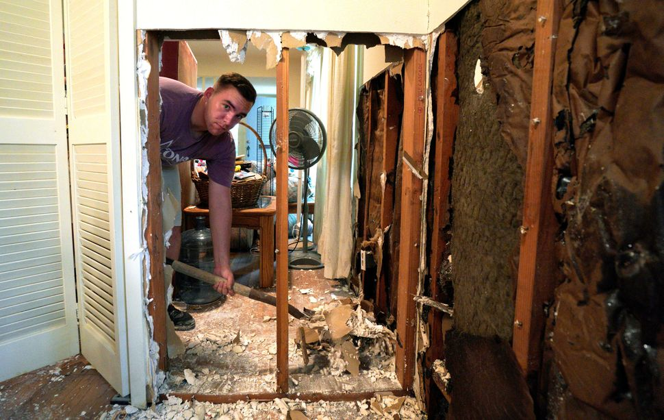 A volunteer from Texas A&M University helps to clean up flood damage in the house of an alumnus in Houston on Sept.