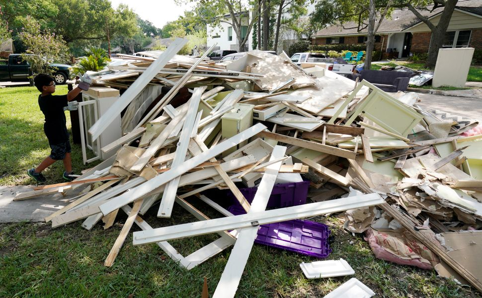 Jay Jackson adds to the pile of trash from Harvey flood damage.