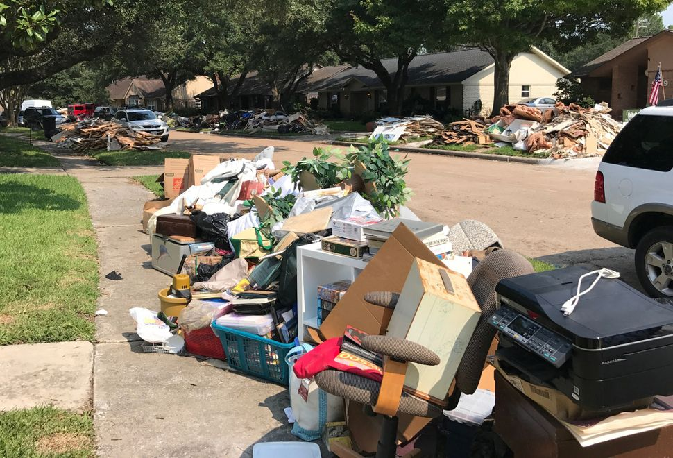 Damaged furniture, carpets and flooring are piled at a curbside on Sept. 2.