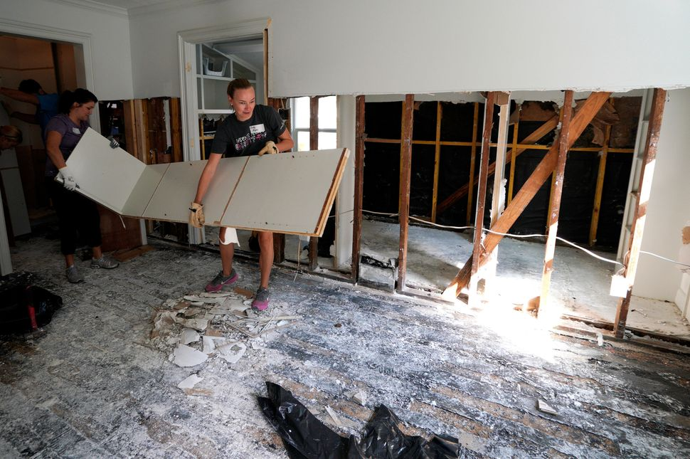 Church volunteers work in a damaged home.