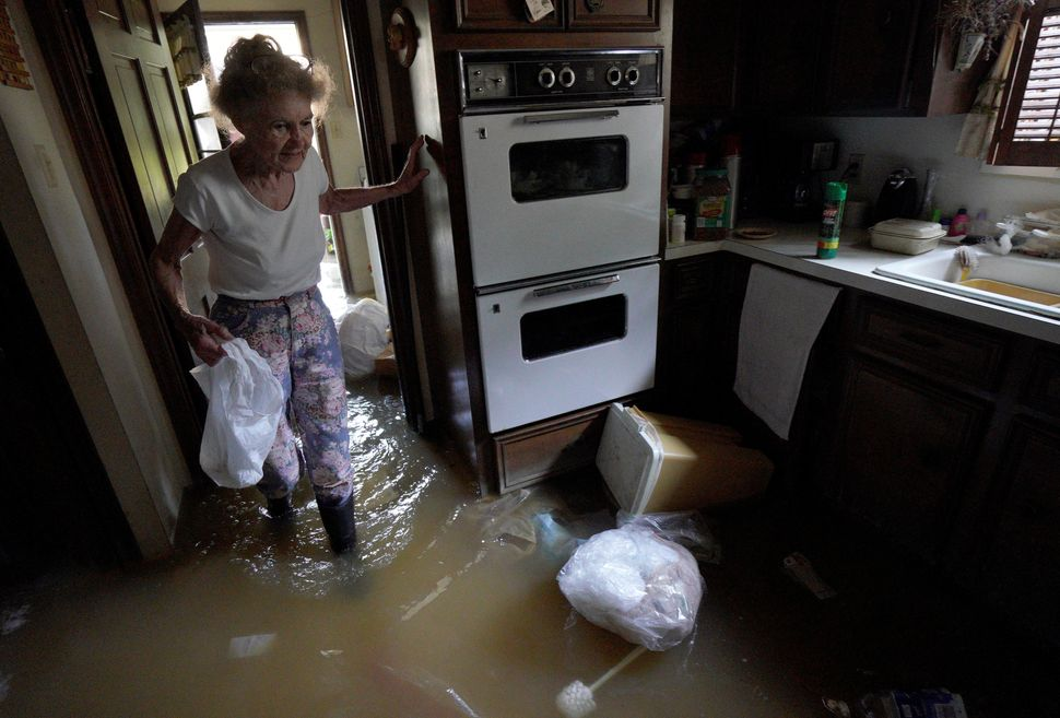 Nancy McBride collects items from her flooded kitchen as she returns to her home on Sept. 1 after the record-breaking rainfal