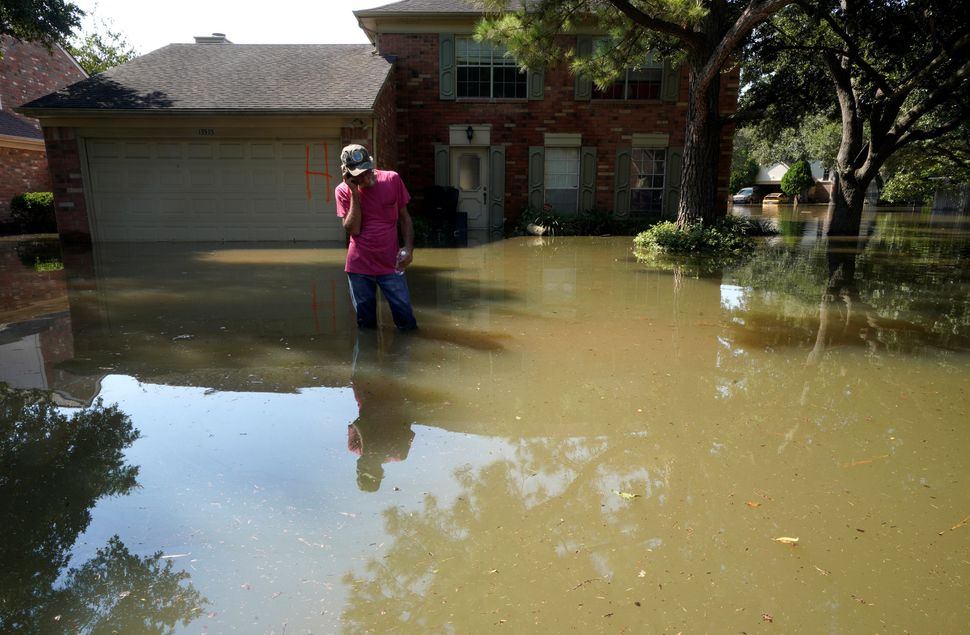 Carl Ellis talks to his daughter stuck in Canada, while standing in front of her house surrounded by Harvey floodwaters on Au