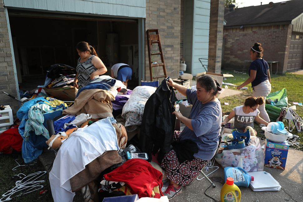 Axa Alvarez (holding coat) and her family sort through clothes on on Sept. 2 as they clean out their house, which had been in