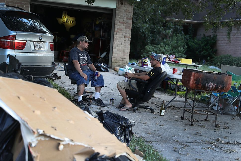 Artemio Tamez and Franco Tamez sit in front of Franco's house on Sept. 2 after spending the day cleaning it out after to