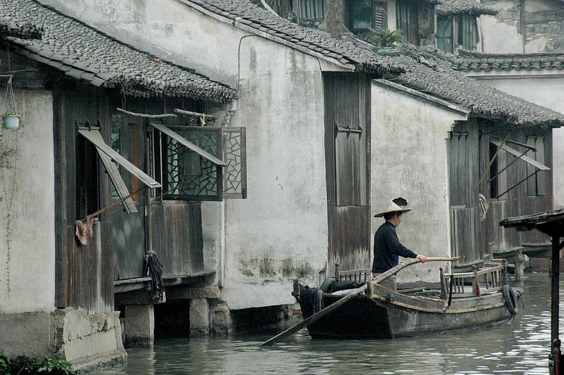 <em>A boatman at Wuzhen, one of the ancient river towns, has been preserved in Zhejiang Province as a living history museum<
