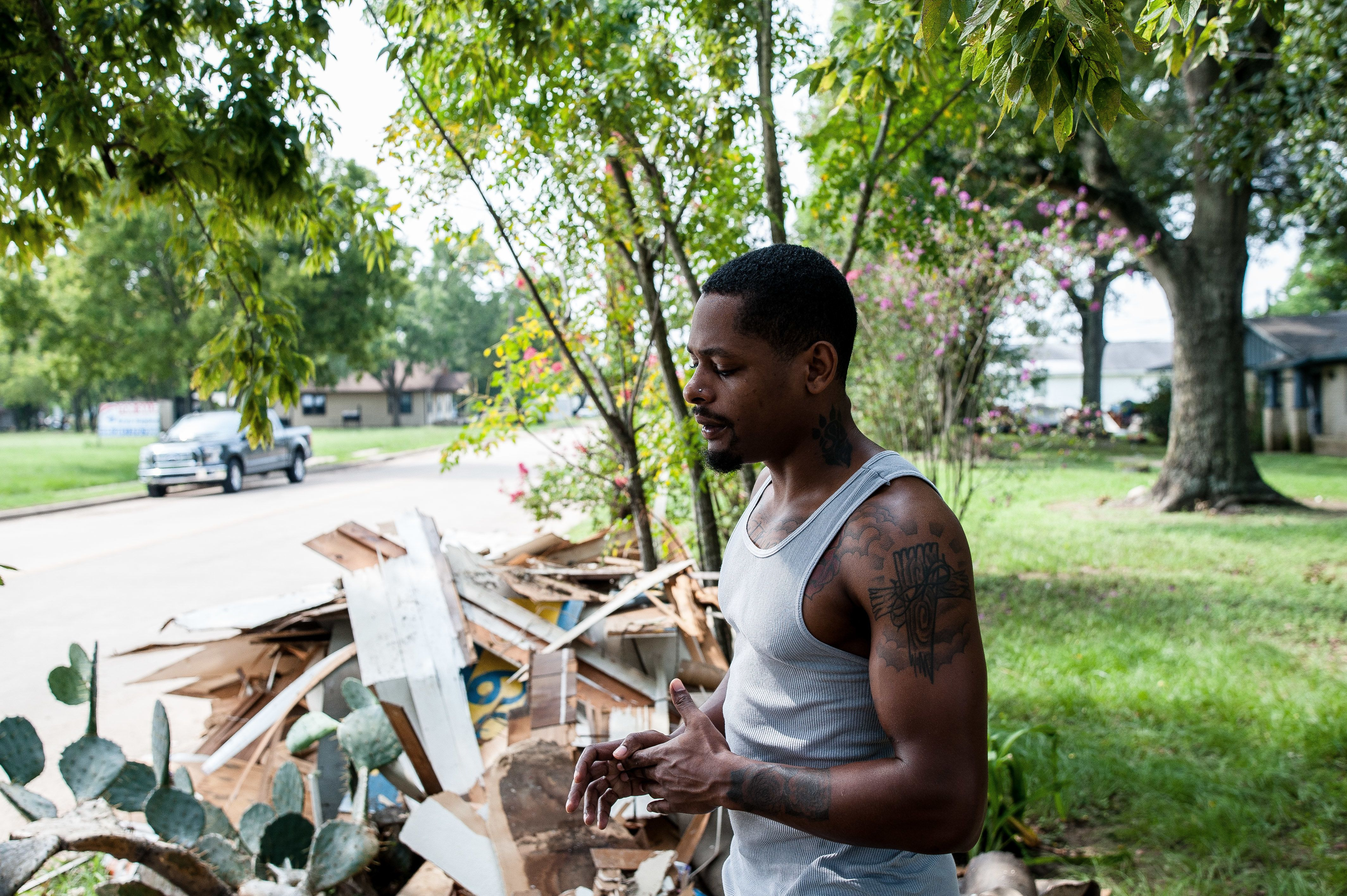 Damion Lasker, 24, stands next to debris on Sunday taken from his mother's flooded home in Katy, Texas,...