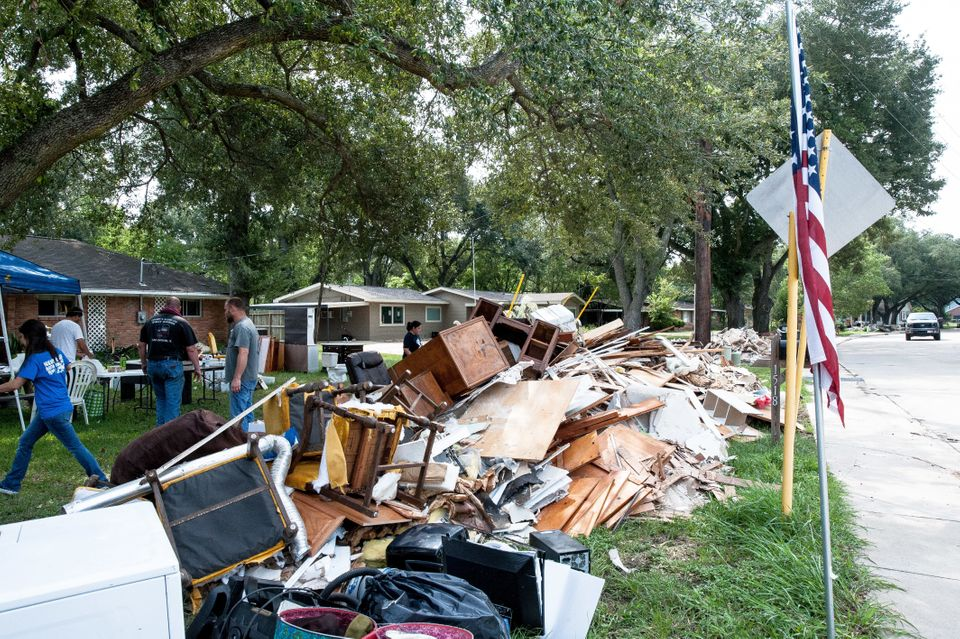 Crewsof volunteers help locals in Katy rip out damaged furniture, roofing, flooring and wood from