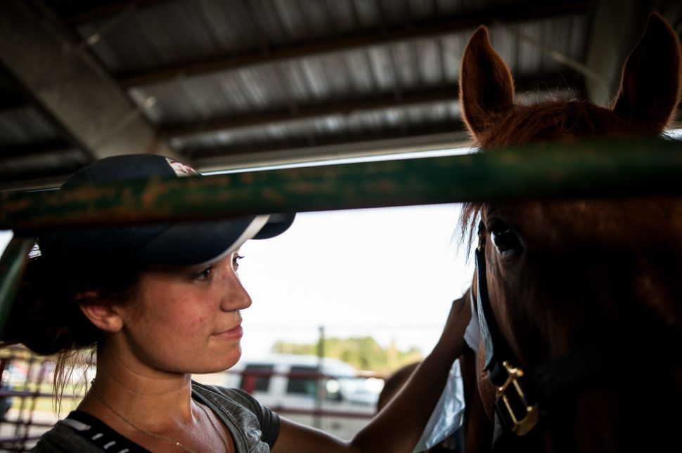 Maggie Olthaus, a vet tech from Columbus, Ohio, pets a horse at Ford Park.