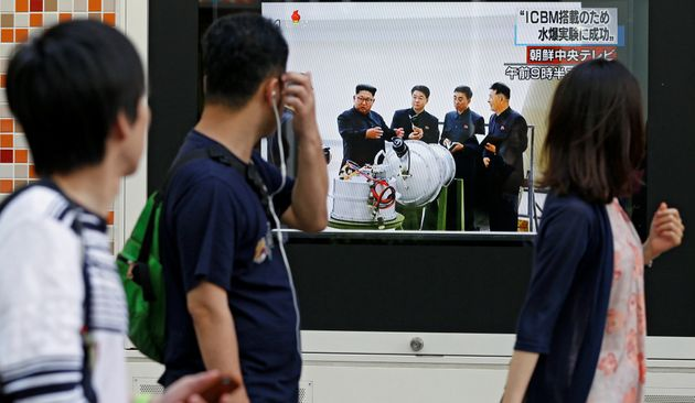 <strong>People walk past a street monitor showing North Korea's leader Kim Jong-Un in a news report...